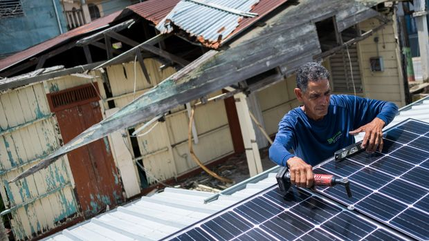 In this July 24, 2018 photo, Julio Rosario instals a solar energy system at a home in Adjuntas, Puerto Rico. The nonprofit environmental group Casa Pueblo has installed solar systems at two hardware stores, one barber shop and several corner stores that activists hope will serve as a power oasis where people can charge their phones and store medications during a storm if needed. (AP Photo/ Dennis M. Rivera Pichardo)