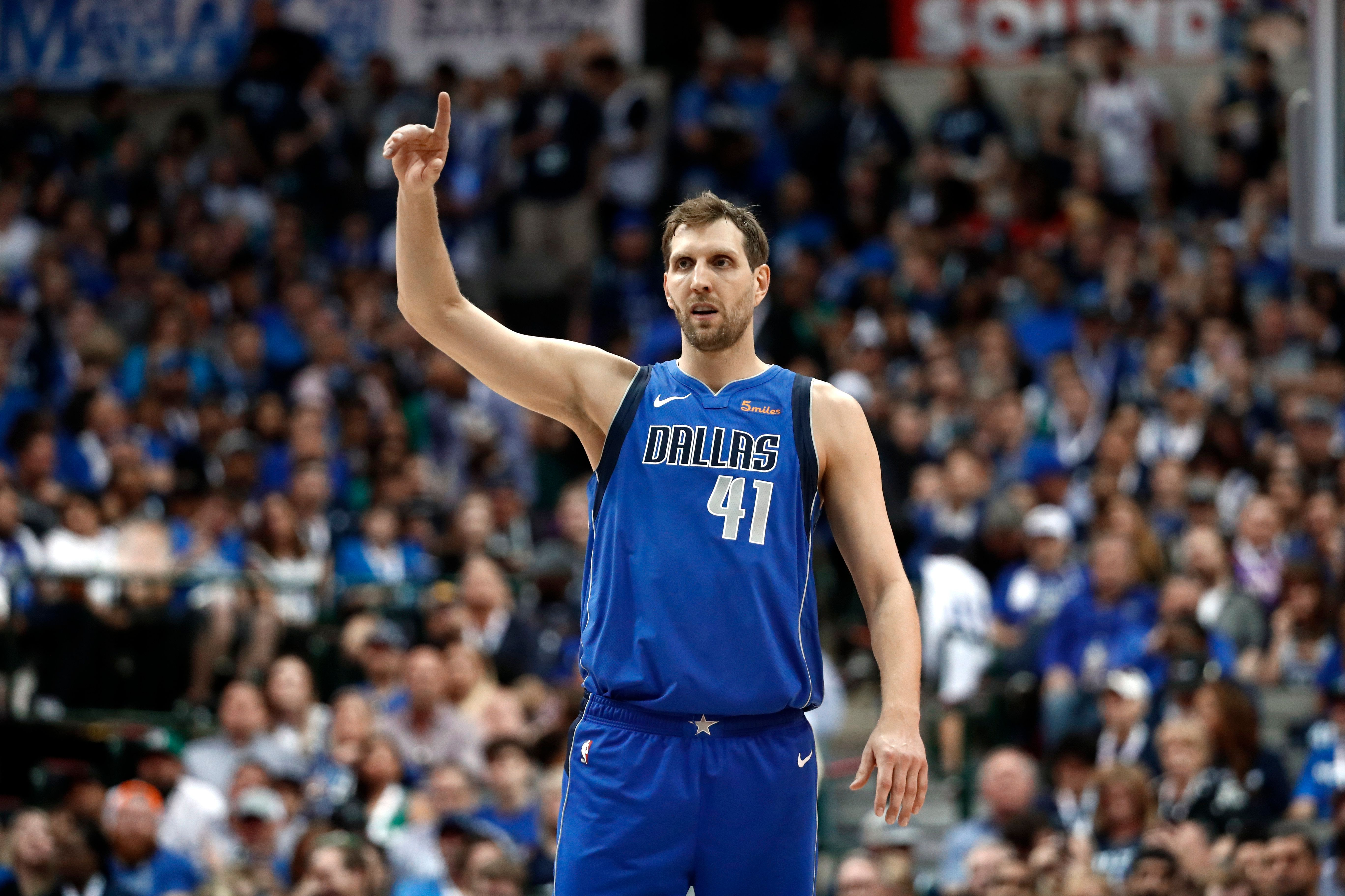 Dallas Mavericks' Dirk Nowitzki celebrates a teammate's basket during the second half of an NBA basketball game against the Phoenix Suns in Dallas, Tuesday, April 9, 2019. (AP Photo/Tony Gutierrez)