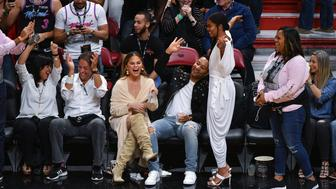 MIAMI, FL - APRIL 09:  Gabrielle Union reacts to the crowd after Dwyane Wade #3 of the Miami Heat made a three point shot while Chrissy Teigen and John Legend look on in the final regular season home game against the Philadelphia 76ers at American Airlines Arena on April 09, 2019 in Miami, Florida. NOTE TO USER: User expressly acknowledges and agrees that, by downloading and or using this photograph, User is consenting to the terms and conditions of the Getty Images License Agreement.  (Photo by Mark Brown/Getty Images)
