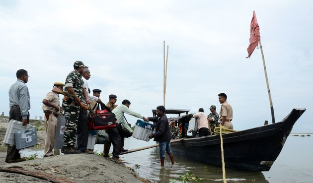Officials carry EVMs on a boat, as security personnel watch over, to reach remote polling stations, in...