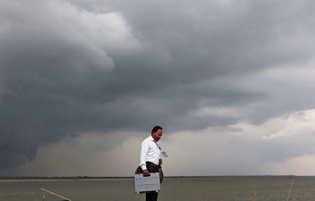 A polling officer carrying an electronic voting machinewalks toward his vehicle after arriving on a ferryboat...