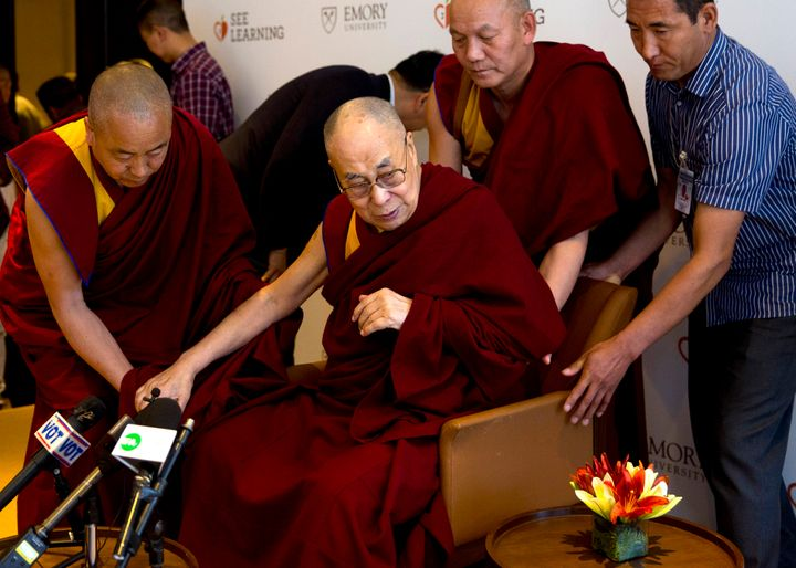 In this April 4, 2019, photo, Tibetan spiritual leader the Dalai Lama, center, is assisted by his aides as he arrives to inte