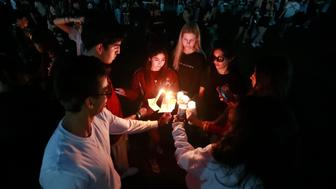 Attendees during an interfaith service light candles, Thursday, Feb. 14, 2019, in Parkland, Fla. More than a thousand people gathered at a South Florida park on the anniversary of the Marjory Stoneman Douglas High massacre to honor the 17 victims killed. (AP Photo/Wilfredo Lee)