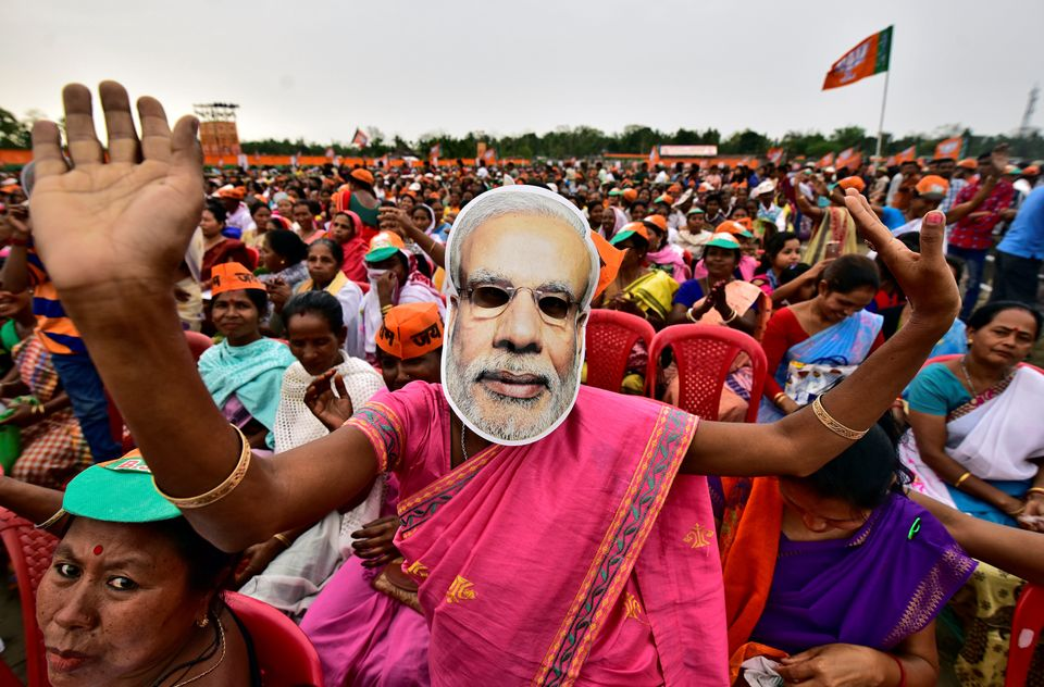 A woman wearing a mask of Prime Minister Narendra Modi dances at an election ally organized by the Bharatiya...