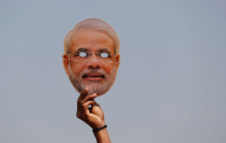 A BJP supporter holds a mask of Prime Minister Narendra Modi during an election rally in Meerut in Uttar Pradesh on March 28, 2019.