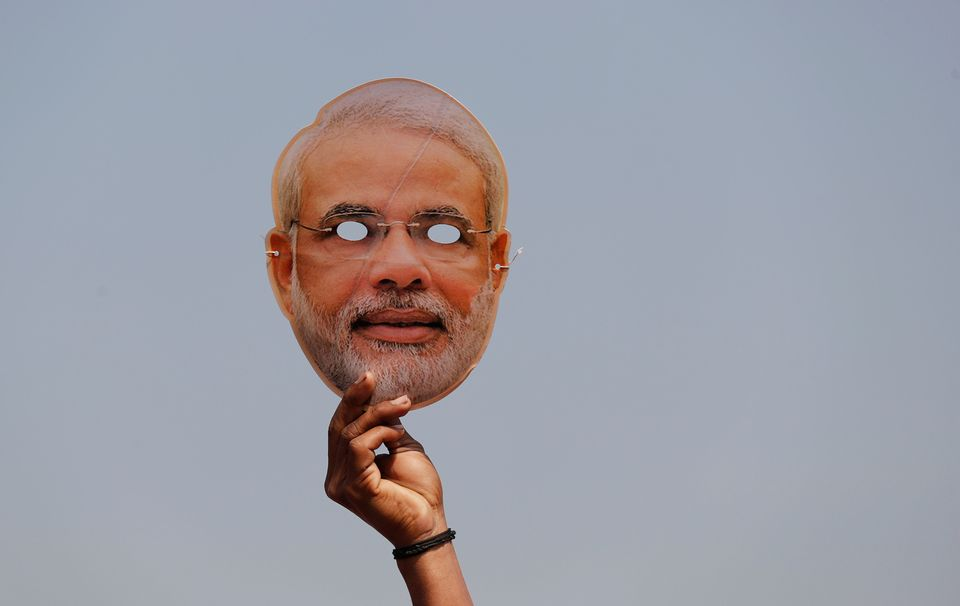 A BJP supporter holds a mask of Prime Minister Narendra Modi during an election rally in Meerut in Uttar...