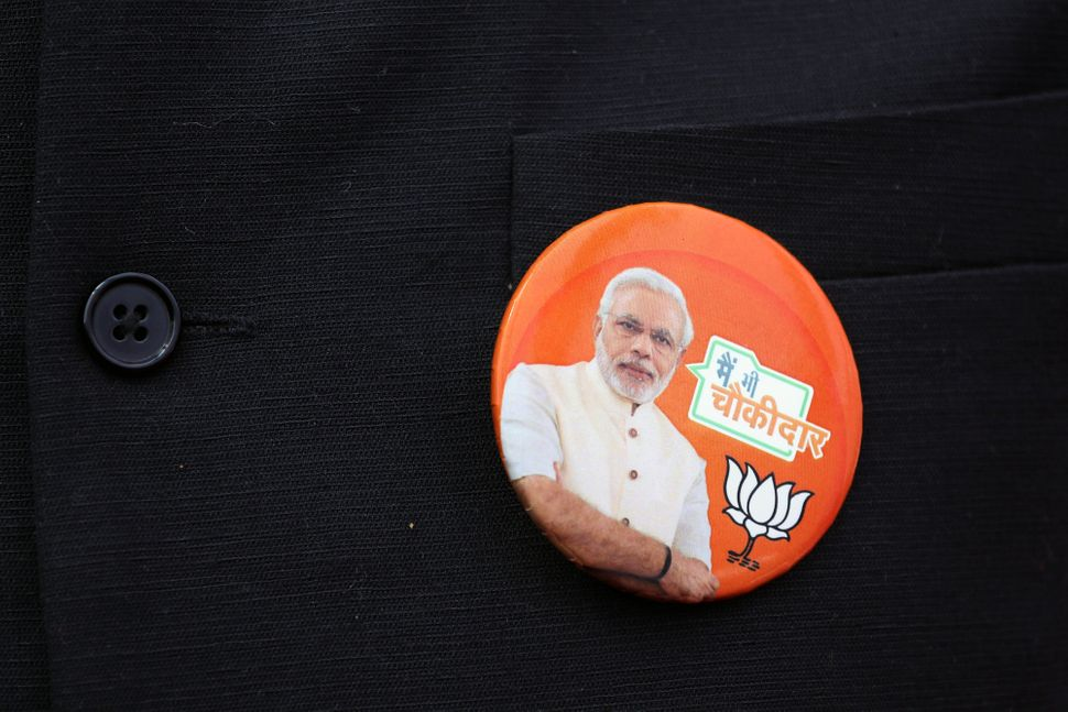 An image of Prime Minister Narendra Modi is displayed on a button during an event marking the release of the Bharatiya Janata