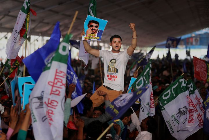 A participant displays a picture of Dalit leader Chandrasekhar Azad as supporters of BSP, SP and RLD gather during an election rally in Deoband on April 7, 2019.