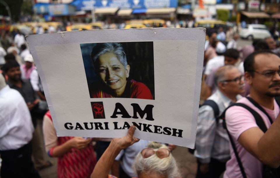 A woman holds a poster of murdered editor Gauri Lankesh on her first death anniversary during a protest...