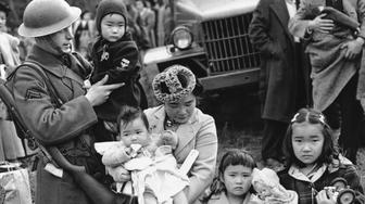 FILE - In this March 30, 1942 file photo, Cpl. George Bushy, left, a member of the military guard which supervised the departure of 237 Japanese people for California, holds the youngest child of Shigeho Kitamoto, center, as she and her children are evacuated from Bainbridge Island, Wash. Roughly 120,000 Japanese immigrants and Japanese-Americans were sent to desolate camps that dotted the West because the government claimed they might plot against the U.S. (AP Photo/File)