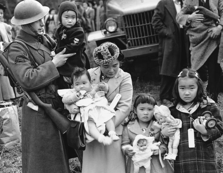 In this March 30, 1942 file photo, Cpl. George Bushy holds the child of Shigeko Kitamoto, center, as her family and other Jap