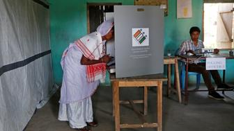 A woman casts her vote at a booth next to a polling officer at a polling station in Majuli, a large river island in the Brahmaputra river, in the northeastern Indian state of Assam, India April 11, 2019. REUTERS/Adnan Abidi