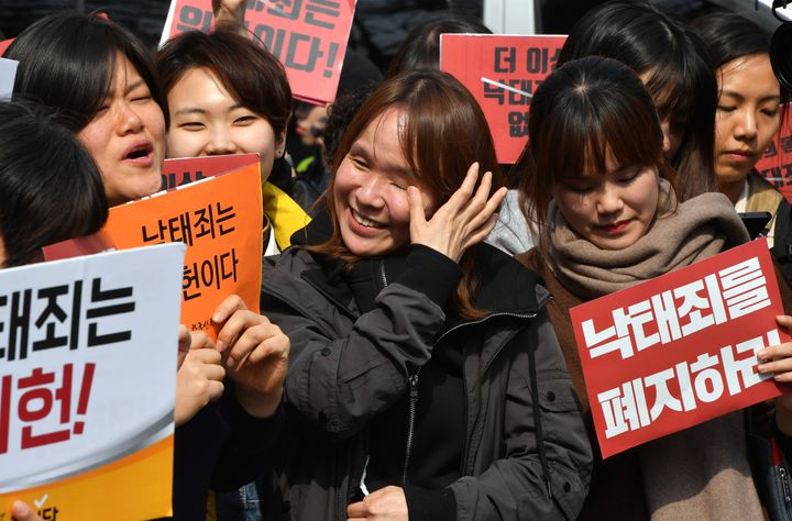 South Korean women's rights activists react after the constitutional court's ruling on decriminalisation of abortion during a