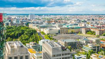 Aerial vista over the green foliage of the Tiergarten to the iconic facade and glass dome of the Reichstag, the Brandenburg Gate and Unter den Linden in the the heart of Berlin, Germany's vibrant capital city.