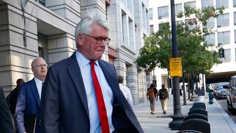 Retired Marine Gen. James Cartwright, center, and attorney Greg Craig, right, leave US District Court in Washington, Monday, Oct. 17, 2016. Cartwright has been charged with making false statements during a federal investigation into leak of classified information contained in a book by New York Times journalist David Sanger, according to charging documents unsealed by prosecutors. (AP Photo/Pablo Martinez Monsivais)