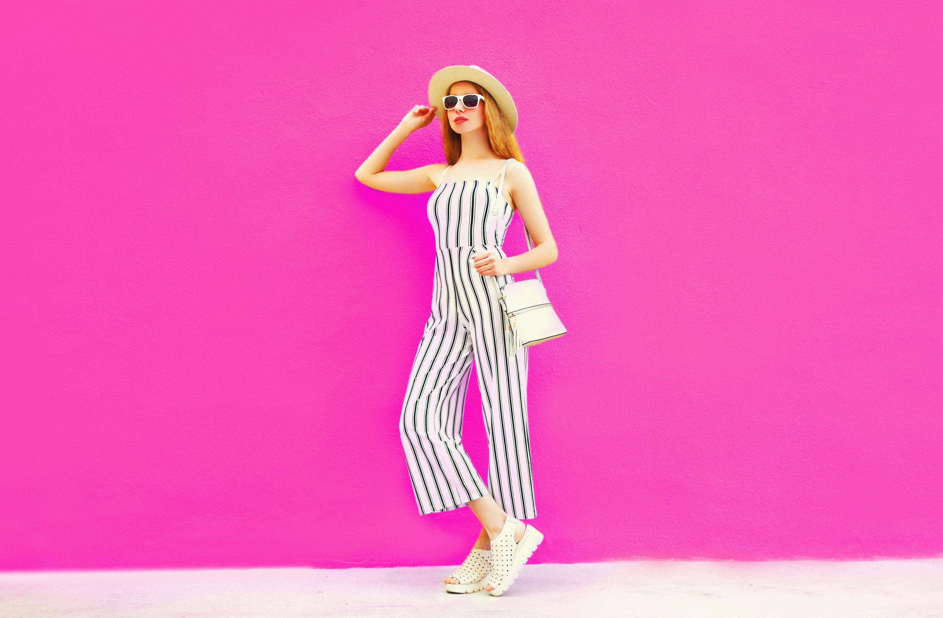 stylish woman model in summer round straw hat, white striped jumpsuit posing on colorful pink wall background