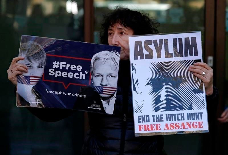 """A protester holds banners reading """"Free speech, except war crimes"""" and """"Asylum: End the witch hunt, free Assange"""" outside Wes"""