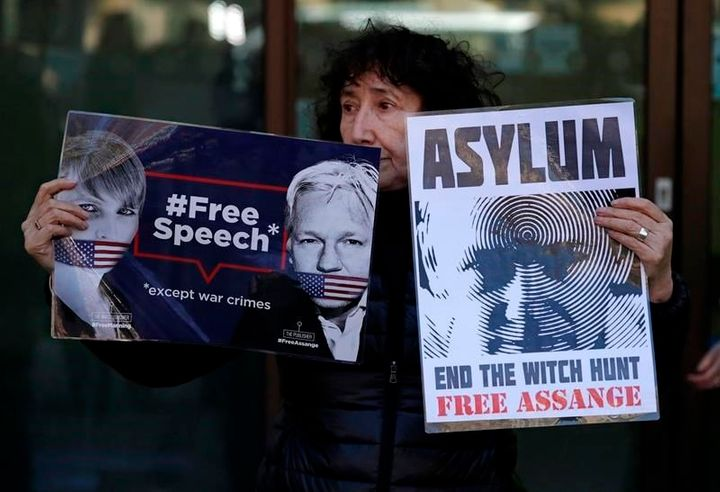 "A protester holds banners reading ""Free speech, except war crimes"" and ""Asylum: End the witch hunt, free Assange"" outside Wes"