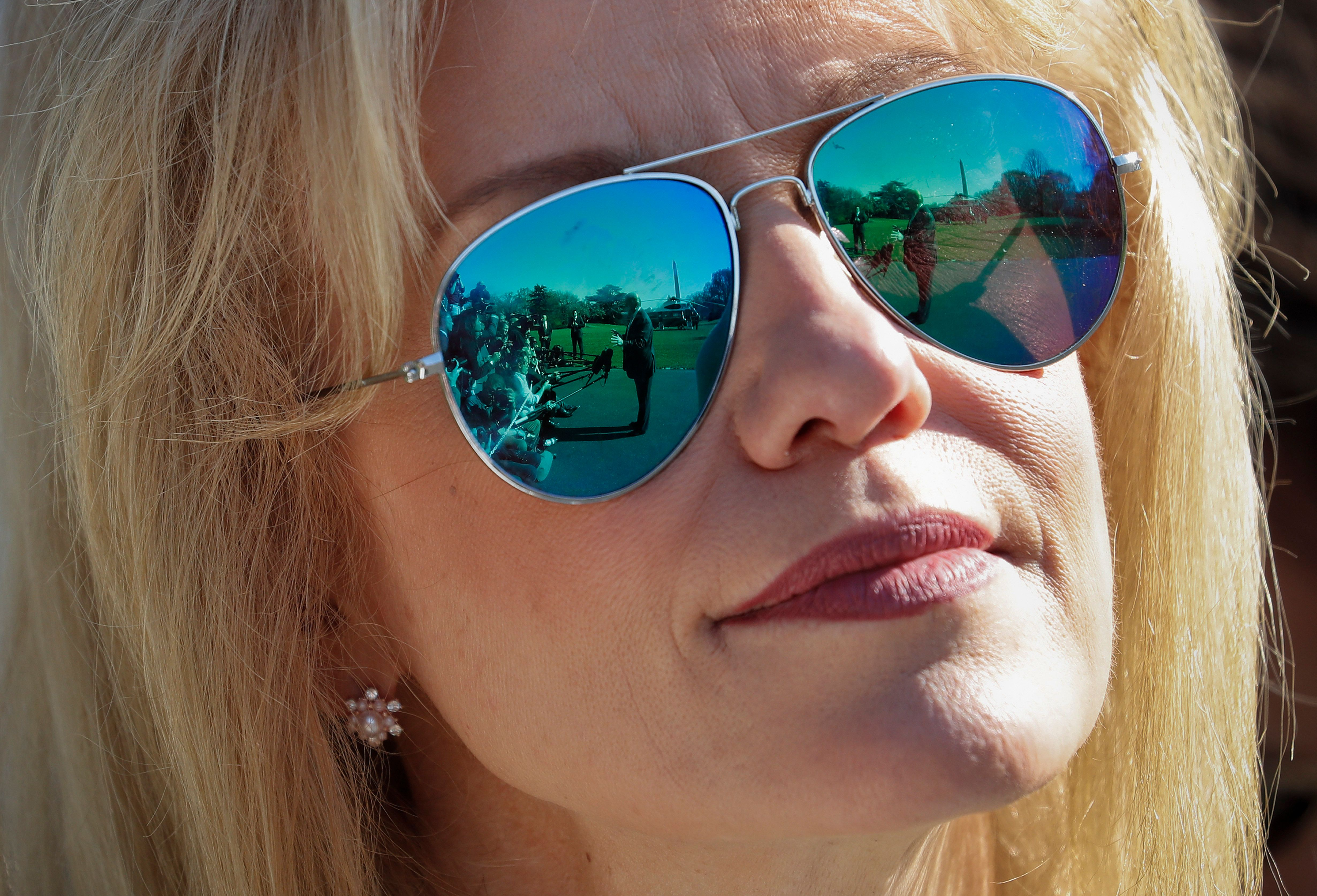 President Donald Trump is seen reflected in the sunglasses of Counselor to the President Kellyanne Conway as Trump speaks to members of the media on the South Lawn of the White House in Washington, before boarding Marine One helicopter, Wednesday, April 10, 2019. (AP Photo/Pablo Martinez Monsivais)