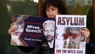 LONDON, UNITED KINGDOM - APRIL 11: A protester holds banners reading 'Free Speech - Except War Crimes - Asylum - End The Witch Hunt Free Assange' during a protest outside Westminster Magistrates court, in London, United Kingdom on April 11, 2019. The Wikileaks co-founder was arrested earlier today after taking refuge at the Ecuadorian embassy seven years ago to avoid extradition to Sweden.  (Photo by Kate Green/Anadolu Agency/Getty Images)