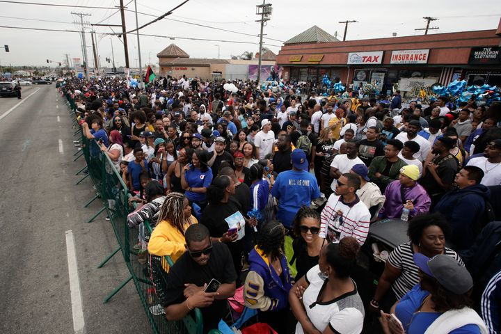 People gather outside The Marathon Clothing store to watch a funeral procession of rapper Nipsey Hussle, Thursday, April 11,