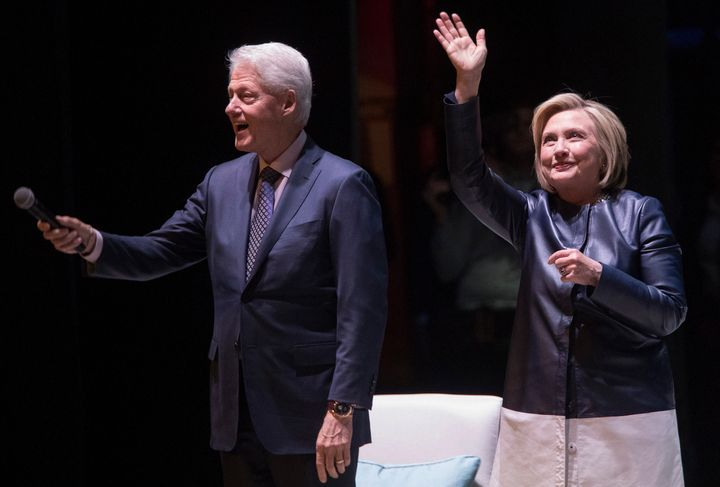 Former President Bill Clinton and former Secretary of State Hillary Clinton wave at the crowd as they arrive on stage Thursda