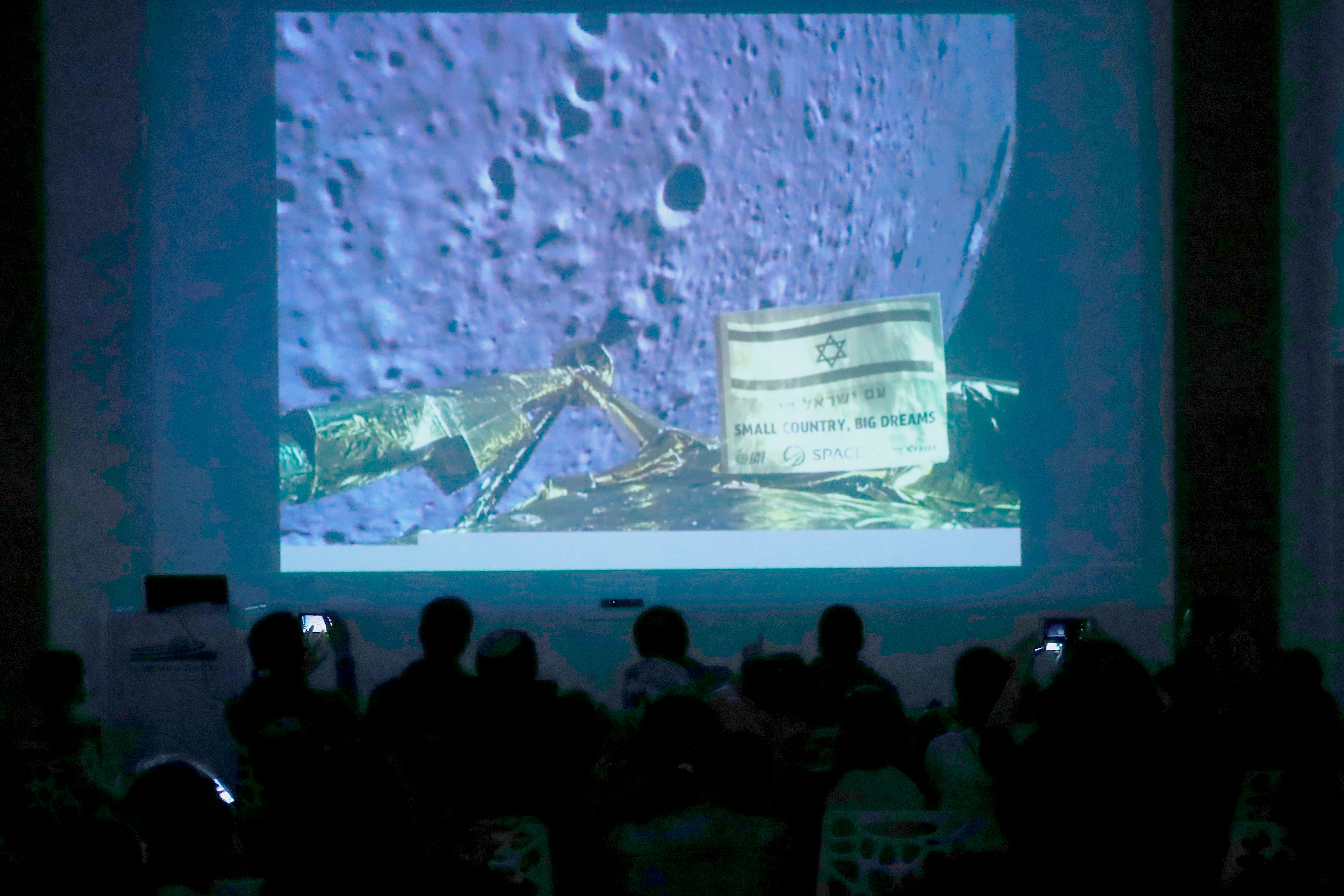 People watch a screen showing a picture taken by the camera of the Israel Beresheet spacecraft of the moon surface as the craft approaches and before it crashed during the landing at the 'Planetaya Planetarium' in the Israeli city of Netanya, on April 11, 2019. (Photo by JACK GUEZ / AFP)        (Photo credit should read JACK GUEZ/AFP/Getty Images)