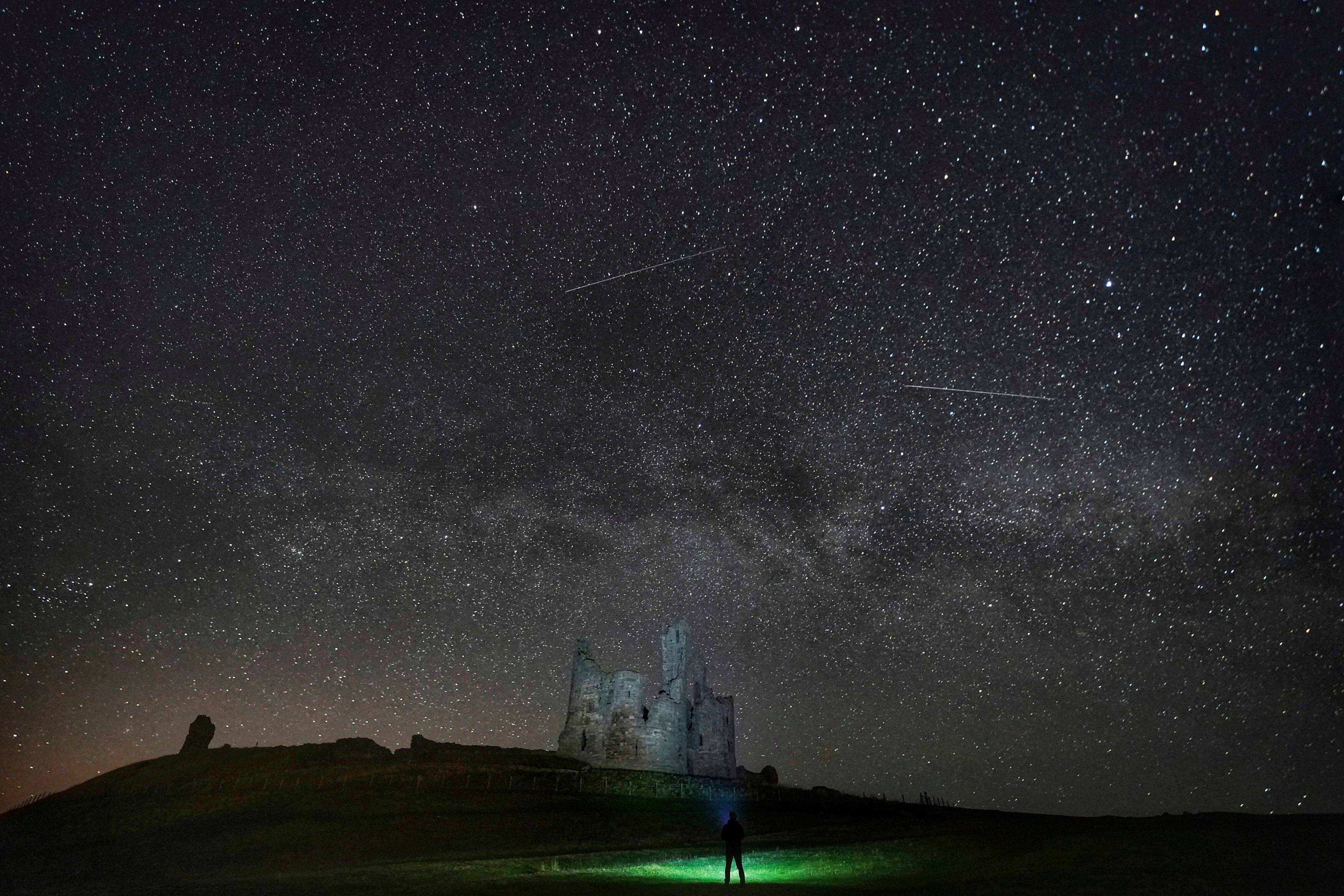Stars over Dunstanburgh Castle in the early hours of the morning, between the villages of Craster and Embleton, in Northumberland, England, Thursday April 11, 2019.  (Owen Humphreys/PA  via AP)