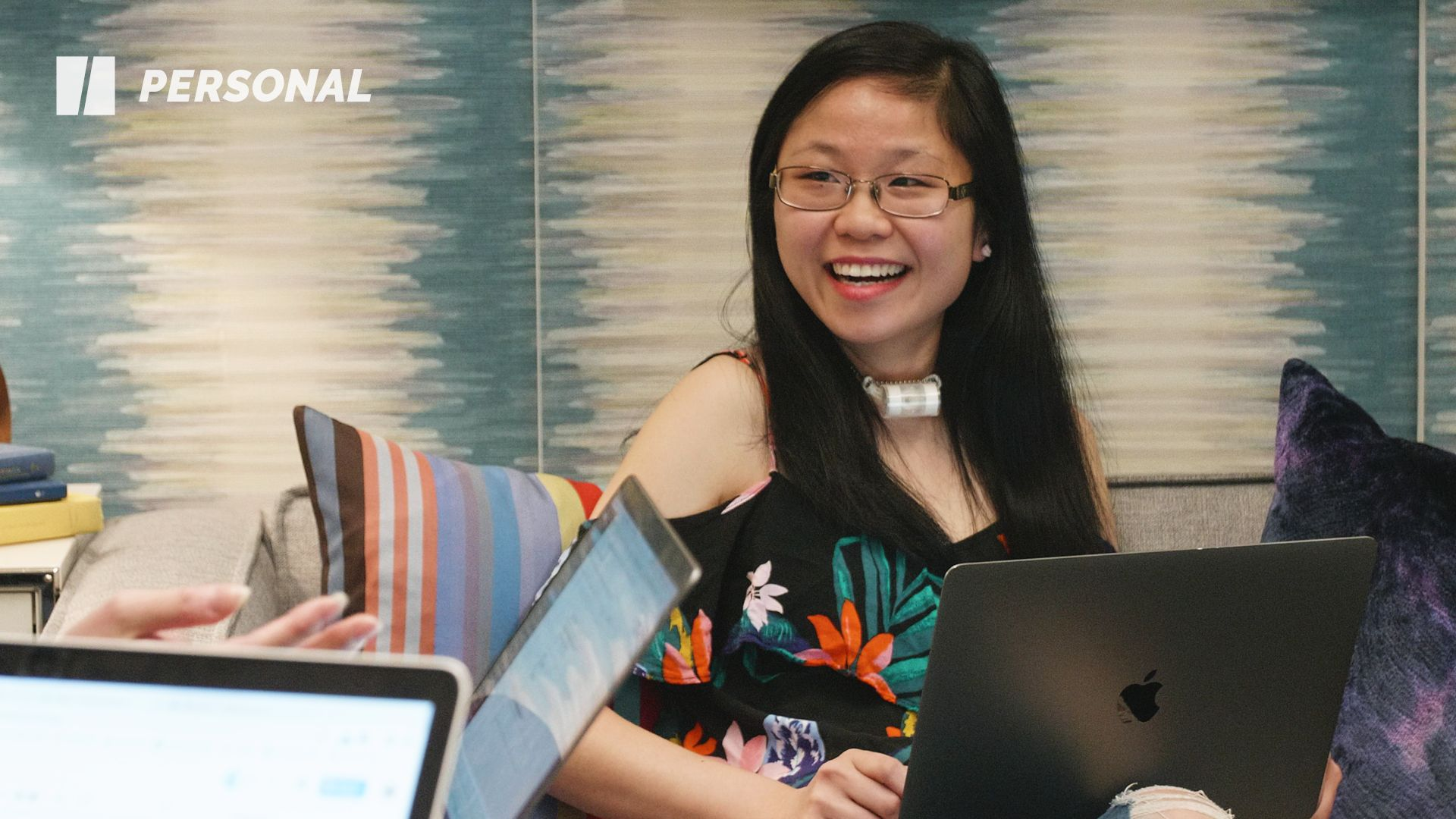 Wendy Lu, a young Asian American woman, sits and smiles on a couch with a colorful pillow nearby in front of a blue and white background.