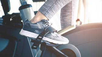 Woman feet is cycling on fitness exercising bike machine