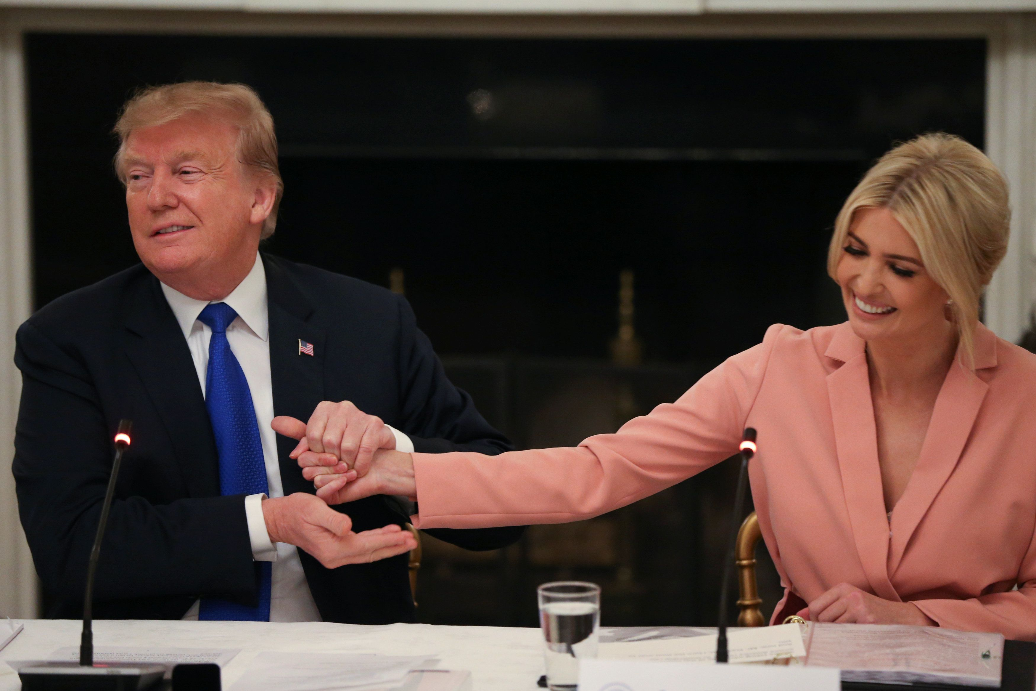 U.S. President Donald Trump grabs the hand of White House senior advisor and his daughter Ivanka Trump as they participate in an American Workforce Policy Advisory Board meeting in the White House State Dining Room in Washington, U.S., March 6, 2019. REUTERS/Leah Millis?