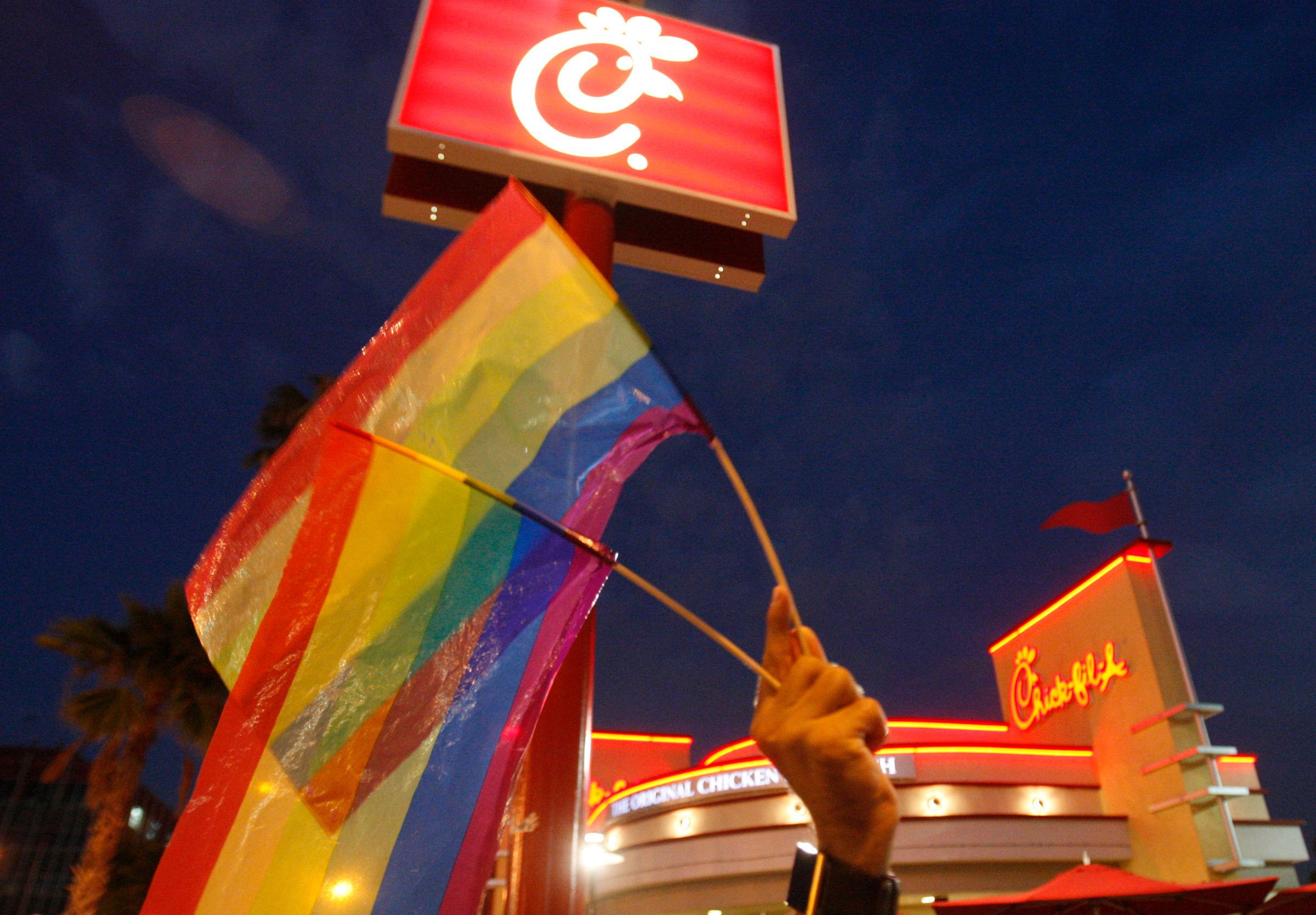 Thomas Guastavino, of the Cuddles gay men's choir, holds up gay pride flags while joining a group of gay–rights and same–sex marriage supporters protesting in front of Chick–fil–A restaurant in Hollywood Friday, August 3, 2012. LGBT supporters have declared Friday to be National Same Sex Kiss Day and are encouraging others to show up at Chick–fil–A restaurants nationwide Friday and stage a 'kiss–in.' Some activists are combining the 'kiss–ins' with Friday evening rallies.  (Photo by Allen J. Schaben/Los Angeles Times via Getty Images)