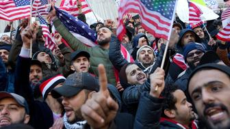 BROOKLYN, NEW YORK - FEBRUARY 2: Members of Brooklyn's Yemeni community hold a rally on the steps of Borough Hall to protest President Trumps's executive order barring immigration from Yemen on February 2, 2017 in downtown Brooklyn.  They waved American flags and chanted 'U.S.A.'. Many Yemen immigrants in New York own or work in bodega grocery stores, which they had shut down for the day in protest. (Photo by Andrew Lichtenstein/Corbis via Getty Images)
