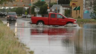 A vehicle drives through a flooded section of Muskingum Avenue on Saturday, April,13, 2019, in Odessa, Texas. (Jacob Ford/Odessa American via AP)