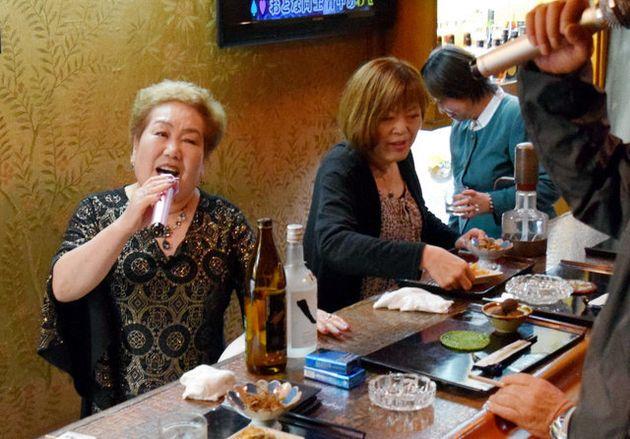 客とカラオケを熱唱する松岡ヒデヨさん(左)=熊本市東区