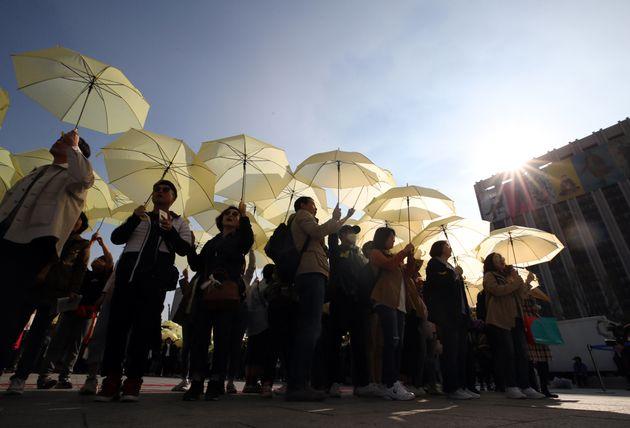 14일 오후 4시 16분에 서울 광화문광장에서 세월호 참사 5주기 '잊지 않을게' 대학생 대회에서 참가자들이 노란 우산으로 세월호 리본을 만드는 퍼포먼스를 하고