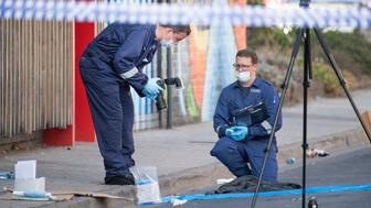 Forensic police examine items at the scene of a multiple shooting outside Love Machine nightclub in Melbourne, Sunday, April 14, 2019.  A shooting outside the nightclub early Sunday left at least two people critically wounded, police said. (Ellen Smith/AAP Image via AP)