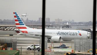 FILE - In a March 13, 2019 file photo, an American Airlines Boeing 737 MAX 8 sits at a boarding gate at LaGuardia Airport in New York. American Airlines said Sunday, April 7, 2019 it is extending by over a month its cancellations of about 90 daily flights as the troubled 737 Max plane remains grounded by regulators. The Boeing-made Max jets have been grounded in the U.S. and elsewhere since mid-March, following two deadly crashes in Ethiopia and Indonesia. (AP Photo/Frank Franklin II, File)