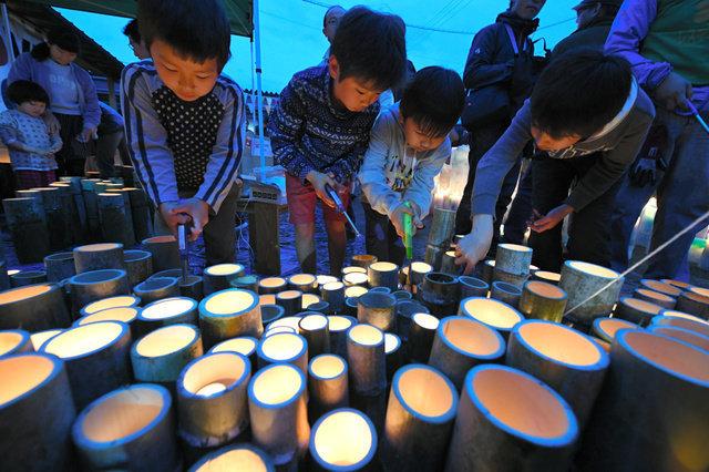 熊本地震から3年となった14日、木山仮設団地の「追悼の集い」で竹灯籠(とうろう)に明かりをつける子どもたち=2019年4月14日午後6時54分、熊本県益城町、日吉健吾撮影