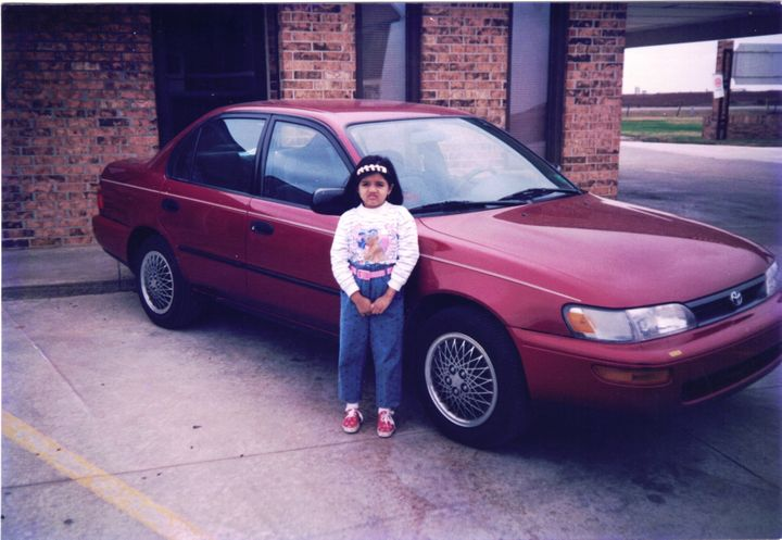 The author, around 5 or 6 years old, standing in front of the family car in rural Oklahoma in front of the motel her parents&