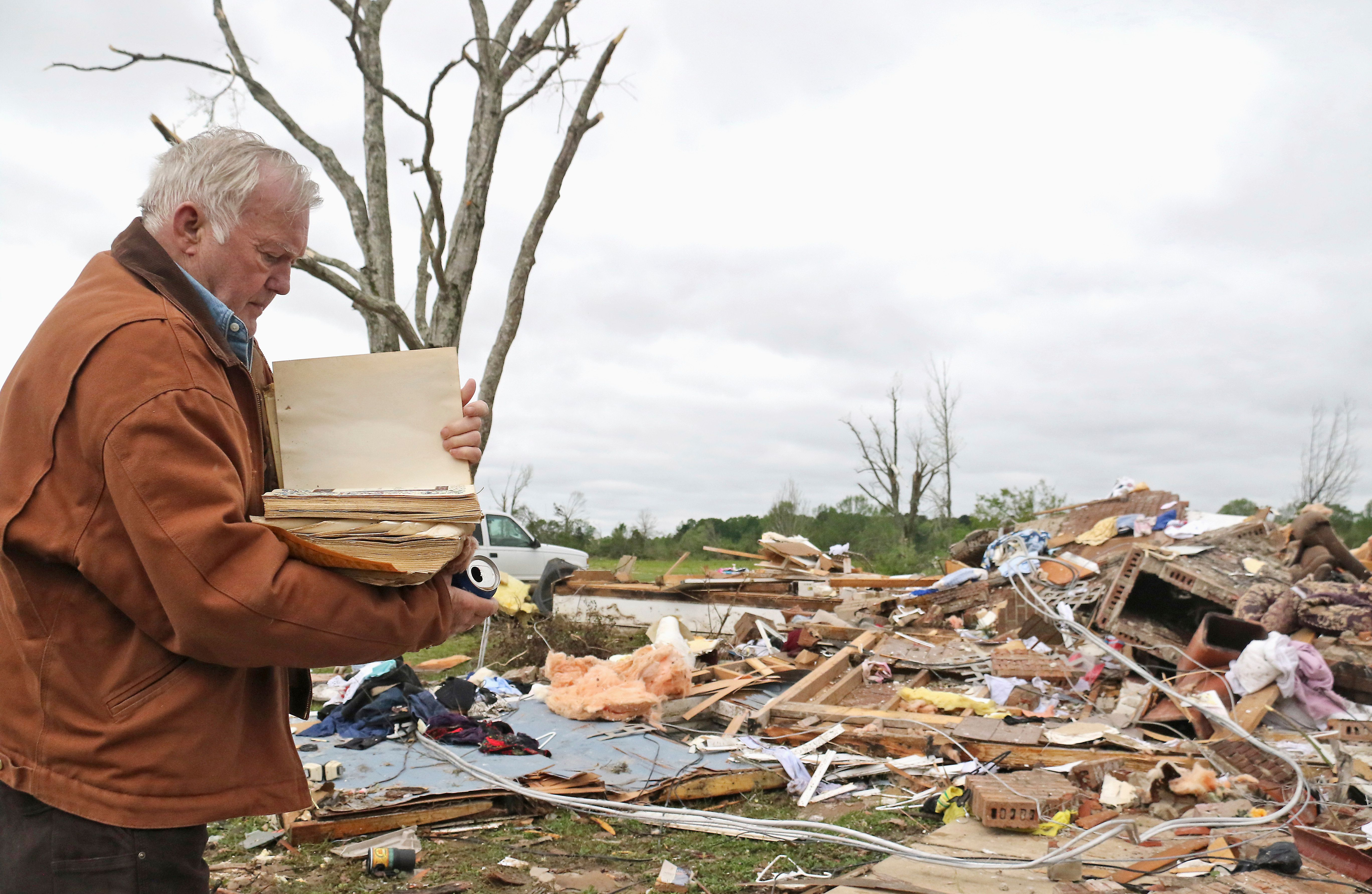 Robert Scott looks through a family Bible that he pulled out of the rubble after a tornado touched down near Hamilton, Missis