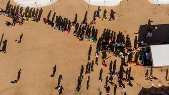 TOPSHOT - An aerial view taken in Beira, Mozambique, on April 1, 2019 shows displaced people queuing for supplies at the Picoco refugee camp. - Cyclone Idai hit the Mozambican coast earlier this month, devastating the port city of Beira and killing at least 700 people in Mozambique, Zimbabwe and Malawi. Cholera has infected at least 1,052 people in Mozambique's cyclone-hit region, the health ministry said on April 1 in a new report, marking a massive increase from 139 cases reported four days ago. (Photo by Guillem Sartorio / AFP)        (Photo credit should read GUILLEM SARTORIO/AFP/Getty Images)