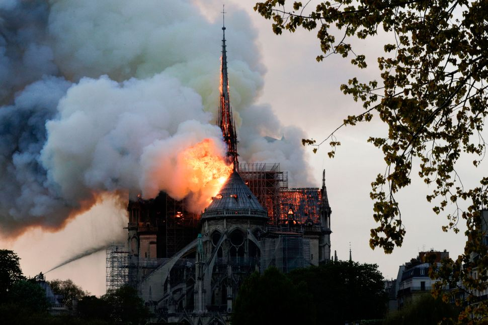 Flames and smoke are seen billowing from the roof at Notre-Dame Cathedral in Paris on April 15, 2019. -