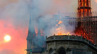 Smoke billows as flames destroy the roof of the landmark Notre-Dame Cathedral in central Paris on April 15, 2019. - A major fire broke out at the landmark Notre-Dame Cathedral in central Paris sending flames and huge clouds of grey smoke billowing into the sky, the fire service said. The flames and smoke plumed from the spire and roof of the gothic cathedral, visited by millions of people a year, where renovations are currently underway. (Photo by FRANCOIS GUILLOT / AFP)        (Photo credit should read FRANCOIS GUILLOT/AFP/Getty Images)