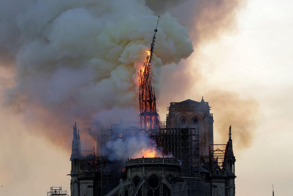 The steeple of the landmark Notre Dame Cathedral collapses as the cathedral is engulfed in flames in central Paris on April 1