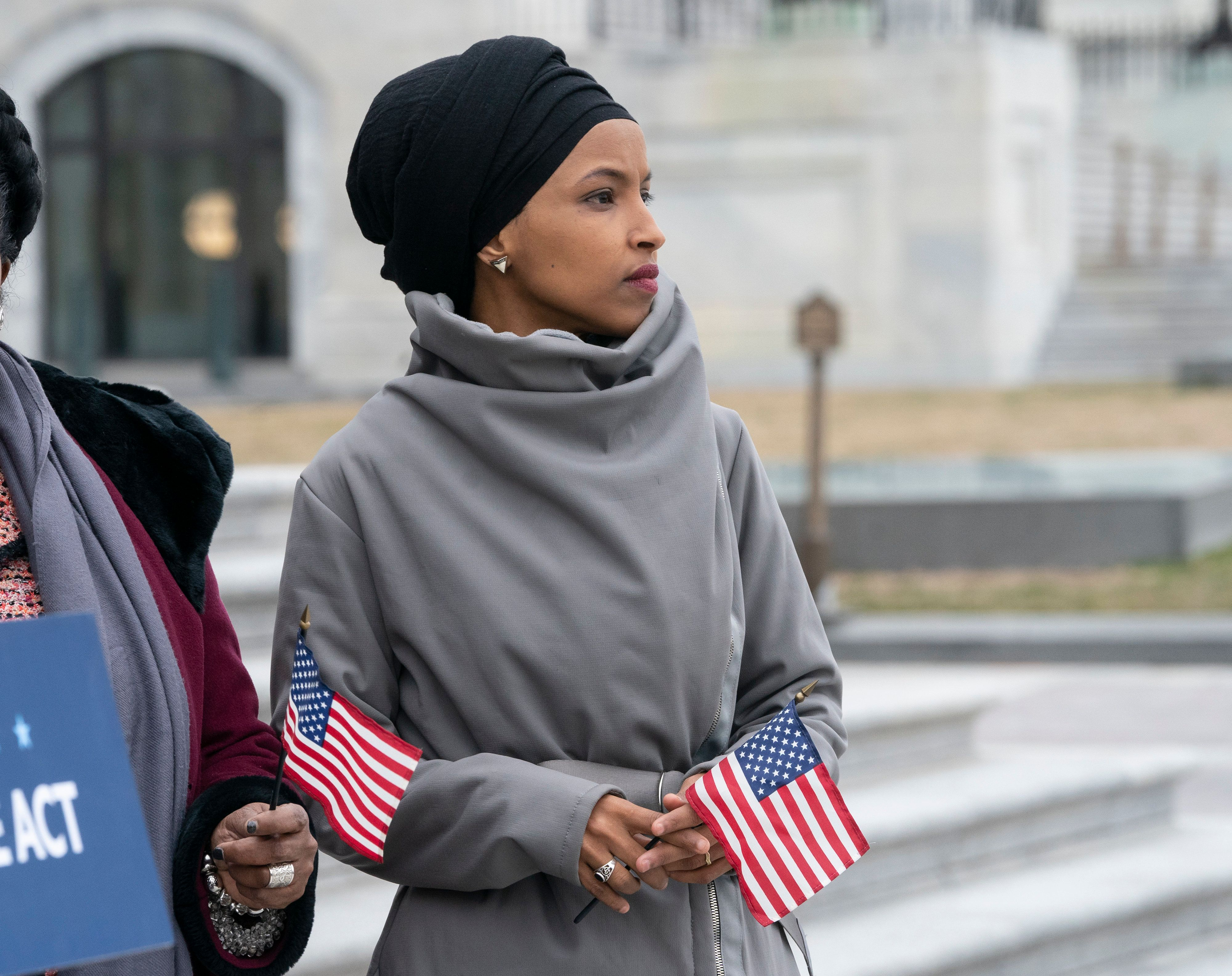 "Rep. Ilhan Omar, D-Minn., stands with fellow Democrats as they rally outside the Capitol ahead of passage of H.R. 1, ""The For the People Act,"" a bill which aims to expand voting rights and strengthen ethics rules, in Washington, Friday, March 8, 2019. The House passed a resolution to condemn anti-Semitism and other bigotry on Thursday following debate over Omar's recent comments suggesting House supporters of Israel have dual allegiances. (AP Photo/J. Scott Applewhite)"