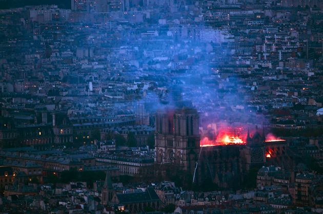 A view from Montparnasse Tower shows flames and smoke billowing from the roof of Notre Dame Cathedral...