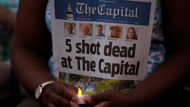 A woman holds a copy of the Capital Gazette during a candlelight vigil to honor the five people who were killed inside the Capital Gazette newspaper the day before in Annapolis, Maryland, U.S. June 29, 2018.  REUTERS/Leah Millis