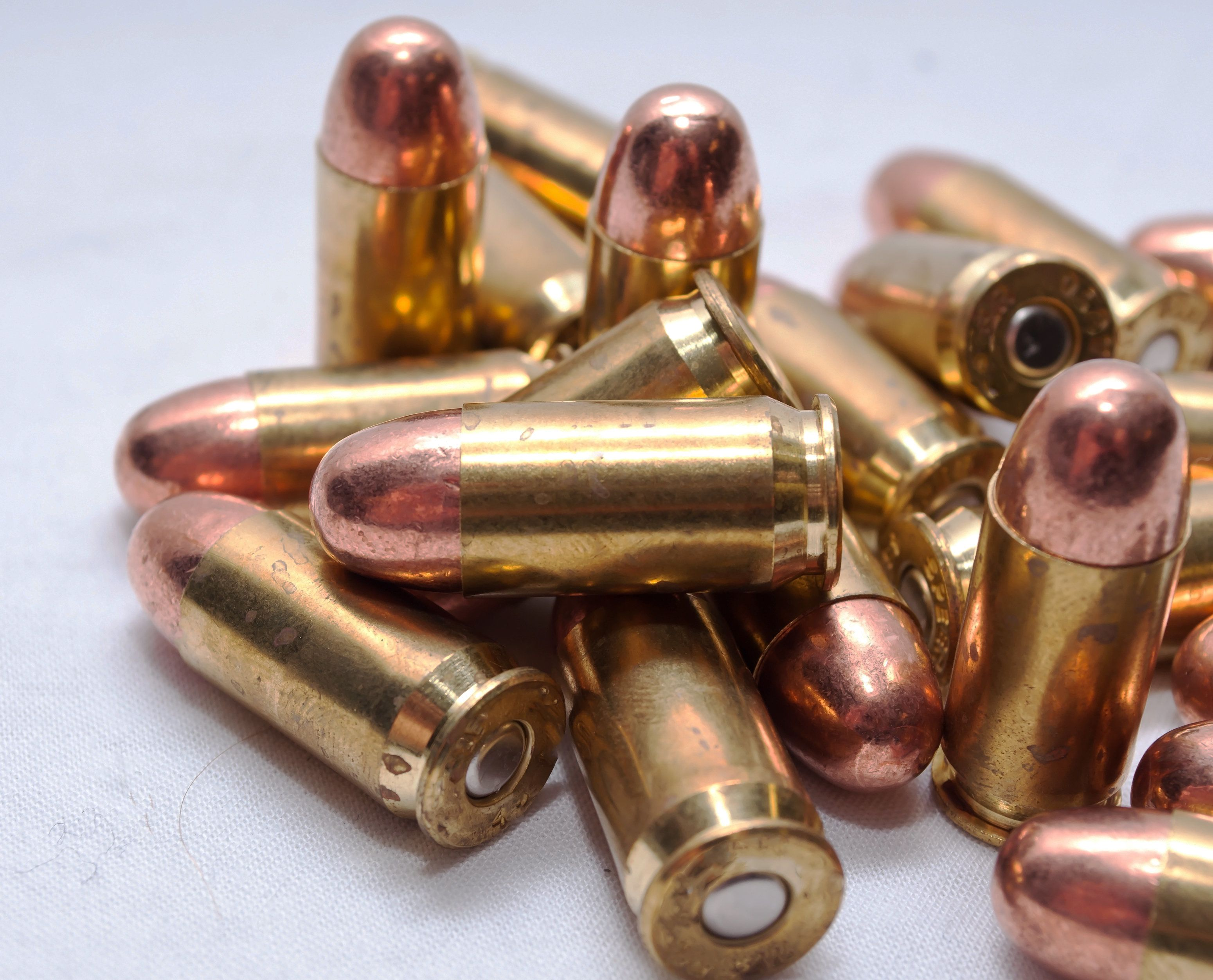 A pile of .45acp full metal jacket bullets on a white background