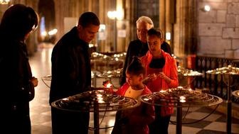 U.S. President Barack Obama and first lady Michelle Obama (L) light a candle with daughters Sasha (C) and Malia (R) in Notre Dame Cathedral in  this handout photo taken in Paris, June 6, 2009 and later released by the White House. Photo is low resolution but highest resolution offered by source. REUTERS/Pete Souza/The White House/Handout  (FRANCE POLITICS) FOR EDITORIAL USE ONLY. NOT FOR SALE FOR MARKETING OR ADVERTISING CAMPAIGNS